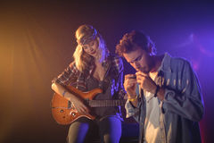 Guitarist performing with musician playing harmonica in nightclub. Female guitarist performing with musician playing harmonica in nightclub Stock Image