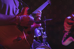 Guitarist performing in nightclub. Mid section of guitarist performing in nightclub Royalty Free Stock Photos