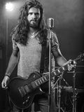 Guitarist performing on stage. Photo of a young man with long hair and beard playing electric guitar on stage Stock Images