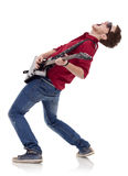 Guitarist playing. Side view of a passionate guitarist playing his electric guitar on white background Royalty Free Stock Photo