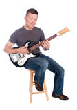 Guitarist playing. Male guitarist strumming his guitar while sitting on a stool, and isolated on white Royalty Free Stock Photo