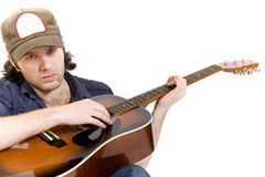 Guitarist playing an acoustic guitar seated Royalty Free Stock Photos