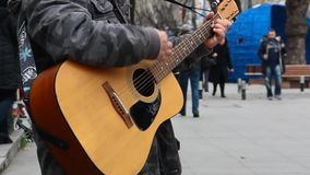 Guitarist playing acoustic guitar in the street stock footage