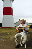 Guitarist playing acoustic near lighthouse Royalty Free Stock Image