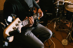Guitarist playing bass guitar in studio closeup. Music band recording process, live rock concert stock images