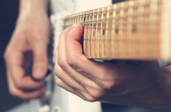 Guitarist playing an electric guitar. Shallow depth of field. Grunge filter royalty free stock photography