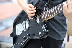 Guitarist playing the guitar, close-up on the guitar royalty free stock photos