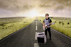 Guitarist playing guitar on the road Royalty Free Stock Image