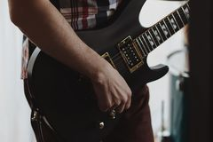 Guitarist playing his acoustic guitar at a local concert with his band and another guitarist in the background.  royalty free stock photography