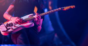 Guitarist playing his vintage guitar on stage. Guitar solo under. Blue, orange, purple lighting. Selective focus Royalty Free Stock Images