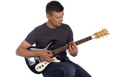 Guitarist playing instrument. Isolated on a white background while sitting on a stool Stock Photos