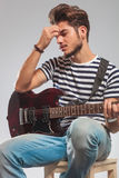 Guitarist playing instrument seated while thinking Royalty Free Stock Photos