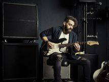 Guitarist playing in a music studio. Photo of a man with beard sitting and playing his electric guitar in a recording studio., smile stock photography