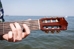 Guitarist playing next to sea. Royalty Free Stock Images
