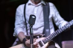 Guitarist playing and singing in a rock concert. Royalty Free Stock Photos