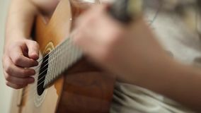 The guitarist plays an acoustic guitar. Guitarist hand and fretboard closeup. Video stock footage