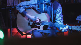 Guitarist plays acoustic guitar and sings microphone in night club, blue lights, close up Royalty Free Stock Images