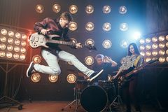 Guitarist plays on bas-guitar, snapshot in a jump. Stage with lights on background. Rock band concert Royalty Free Stock Image
