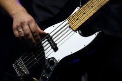 The guitarist plays bass guitar during a rock concert. On the stage Royalty Free Stock Image