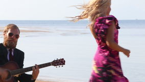 Guitarist plays and blonde girl dances on beach at low tide stock footage