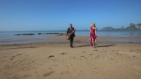 Guitarist plays and blonde girl dances going from sea stock video
