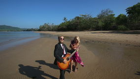 Guitarist plays and blonde girl flirts posing in low tide stock video footage