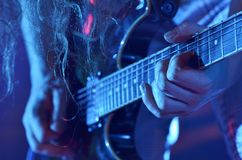 Closeup of a guitar player. The guitarist plays an electric guitar on stage during a concert royalty free stock images