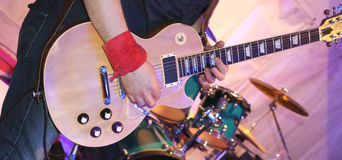 Guitarist plays electric guitar on stage Royalty Free Stock Image