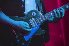 Guitarist plays electric guitar on stage. Guitarist plays electric guitar on a stage, photo with soft selective focus Royalty Free Stock Photo