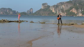 Guitarist plays girl opposite him in sea at low tide stock video