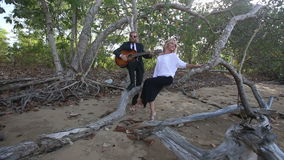 Guitarist plays for girl she smiles and laughs at tropical trees stock video