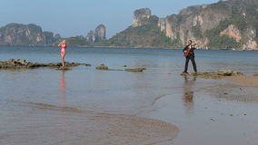 Guitarist plays girl in swimsuit looks at low tide stock footage