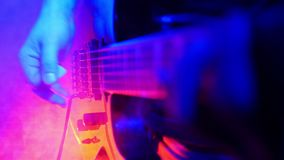 Guitarist plays on his guitar in bright neon lighting. The smoke machine starts working and the room fills up with smoke