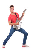 Guitarist plays & looks at you. Casual young man playing his electric guitar and looking at the camera. isolated on a white background Royalty Free Stock Photos