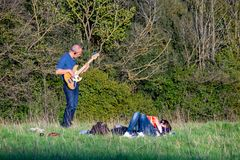 Guitarist plays in the park in the open air. Rome, Italy  03 -23- 2019. Guitarist plays in the park in the open air, while the companion reads a book stock photography