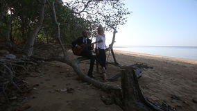 Guitarist plays sitting on branch and girl sits by at trees stock video footage