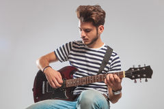 Guitarist pose seated in studio while playing guitar Royalty Free Stock Images