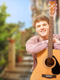 Guitarist posing against summer street view Royalty Free Stock Photography