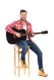 The guitarist posing on a chair Royalty Free Stock Photo