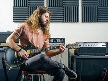 Guitarist recording tracks in the studio. Photo of an attractive man playing electric guitar in a recording studio Royalty Free Stock Photos
