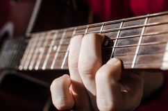 Guitarist. In red shirt. Close-up of a human hand on the strings of red acoustic guitar. Shallow depth of field Stock Photo
