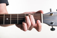 The guitarist`s hand clamps the chord Em on the guitar, on a white background. Horizontal frame Royalty Free Stock Photos