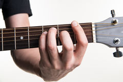 The guitarist`s hand clamps the chord F on the guitar, on a white background. Horizontal frame Royalty Free Stock Photos