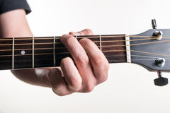 The guitarist`s hand clamps the chord G on the guitar, on a white background. Horizontal frame Stock Images