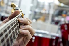 The guitarist`s hand, close-up and soft focus, takes the akrod on a guitar fretboard, against the background of the drum set. The guitarist`s hand, close-up and stock images