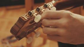 Guitarist`s hands tuning guitar Stock Photo