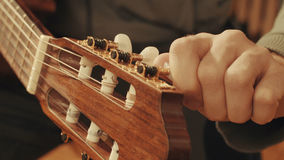 Guitarist`s hands tuning guitar Stock Photography