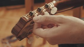 Guitarist`s hands tuning guitar. Close-up 4K stock footage