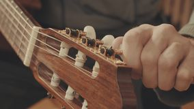 Guitarist`s hands tuning guitar. Close-up 4K stock video footage