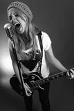 Guitarist screaming into old microphone. Black and white photo of a blond female screaming into an old microphone and playing electric guitar.  High contrast Royalty Free Stock Image